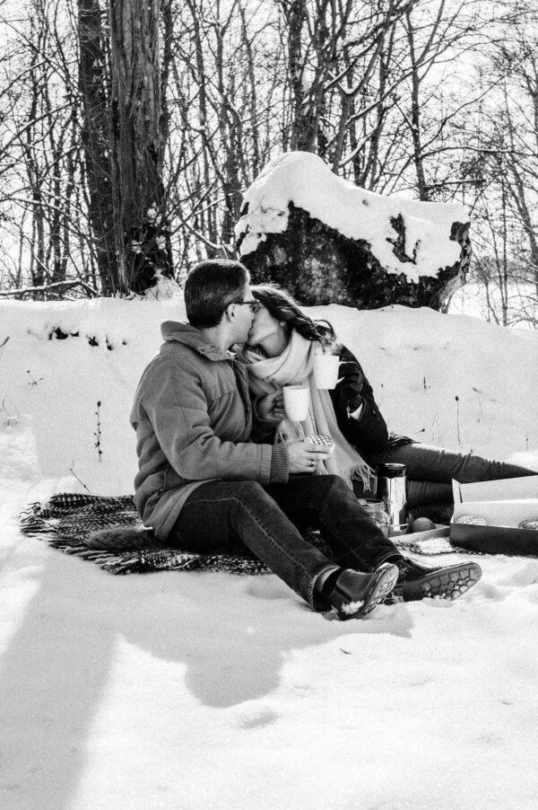 küssendes Pärchen beim Picknick im Schnee in schwarz weiss
