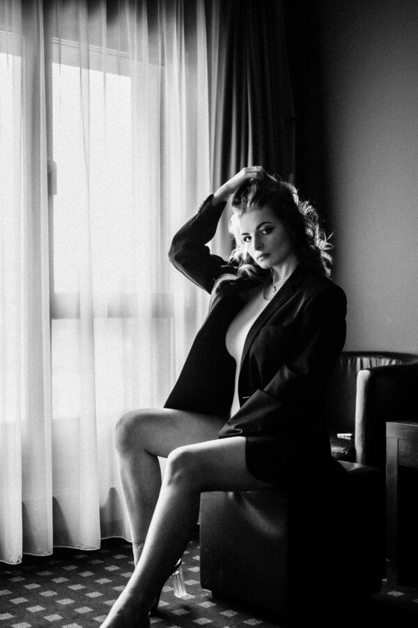 Frauenportrait sitzend mit Männerjacke schwarz weiss