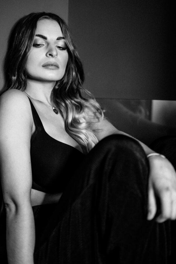 Portrait schöne Frau in schwarz weiss sitzend