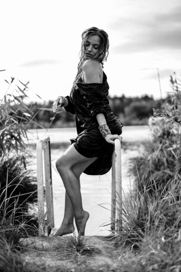 schöne Frau posiert an der Leiter im See