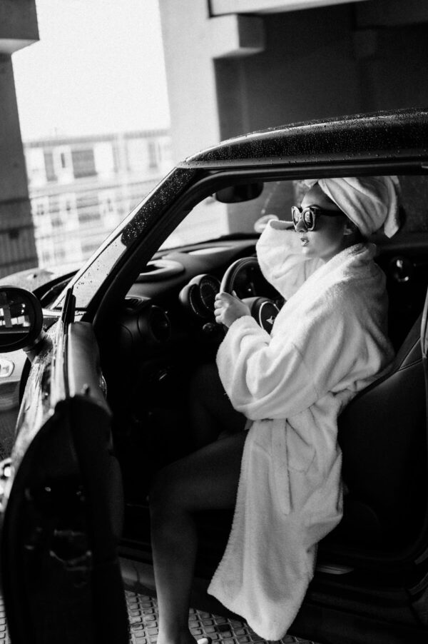 Frau im Bademantel steigt aus dem auto
