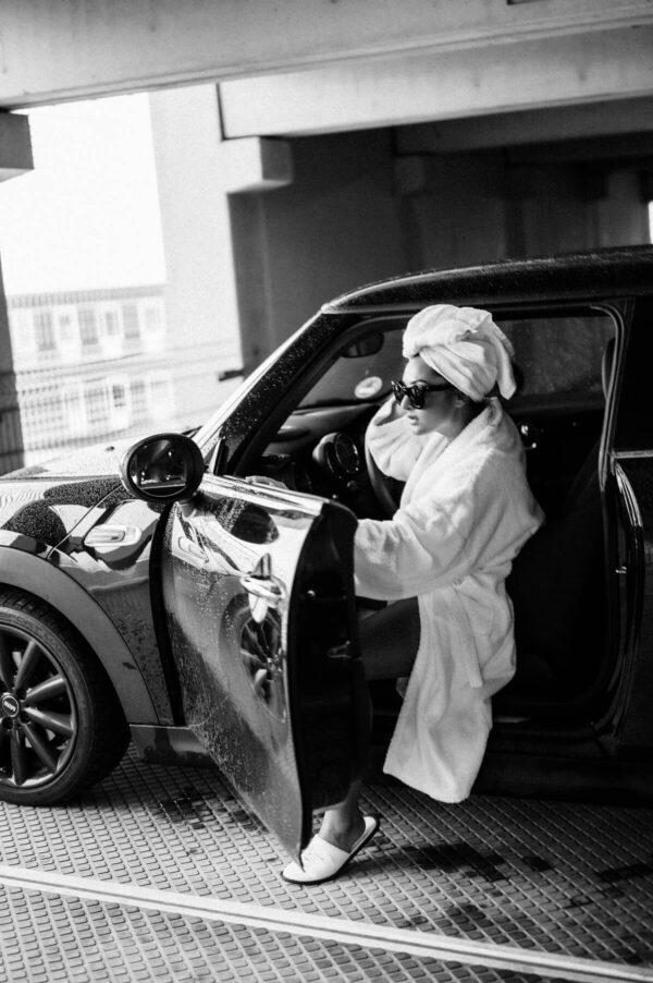 Frau Im Bademantel aus dem Auto aussteigend