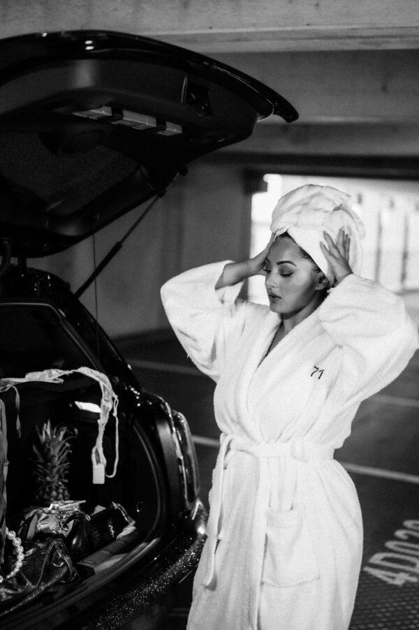 schöne Frau im Bademantel in der Garage