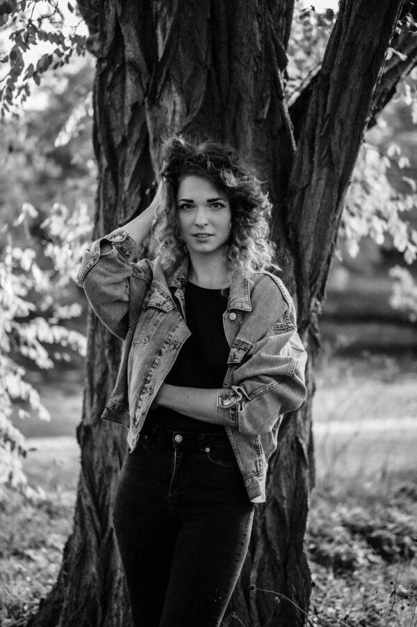 schöne Frau mit locken am Baum stehend
