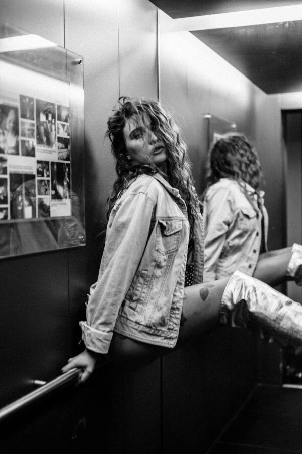 Frau im Aufzug mit Jeansjacke schwarz weiss